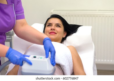 Pretty young woman getting cryolipolyse treatment in cosmetic salon