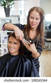 Pretty young woman getting a hair cut by a beautician at parlor
