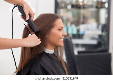 Pretty young woman is getting her hair equalized in beauty salon. The hairdresser is combing her hair and holding an iron. The female client is smiling. Copy space in right side