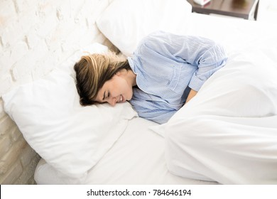 Pretty young woman getting premenstrual  syndrome and huddled up in bed with some pain and discomfort