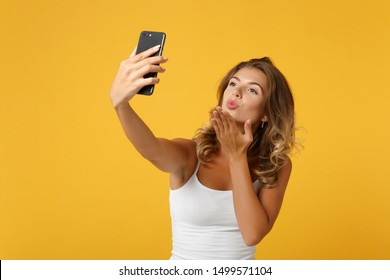 Pretty young woman girl in light casual clothes posing isolated on yellow orange background. People lifestyle concept. Mock up copy space. Doing selfie shot on mobile phone, blowing sending air kiss