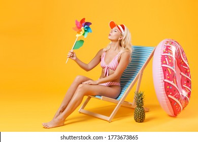 Pretty young woman girl in pink striped swimsuit cap sit on deck chair isolated on yellow background studio. People summer vacation rest lifestyle concept. Mock up copy space. Blowing on toy windmill