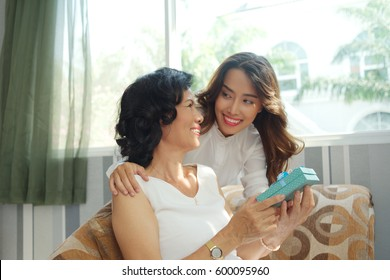 Pretty young woman giving present to her mother