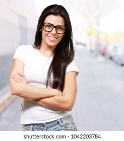 pretty young woman with glasses crossing her arms against a street background