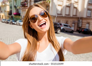 Pretty young woman in glasses having walk and making selfie