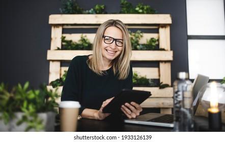 hübsche junge Frau mit Brille sitzt in einem modernen, nachhaltigen Büro mit vielen grünen ökologischen Pflanzen und arbeitet auf ihrem Tablet und ist glücklich