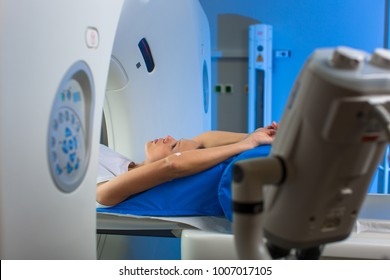 Pretty, young woman goiing through a Computerized Axial Tomography (CAT) Scan medical test/examination in a modern hospital (color toned image; shallow DOF)