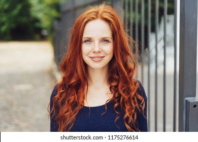 Pretty young woman with gorgeous long curly red hair standing outdoors alongside a metal railing looking at the camera with a quiet thoughtful friendly smile