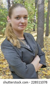 pretty young woman in a gray business dress standing in the autumn forest half-turned with arms crossed