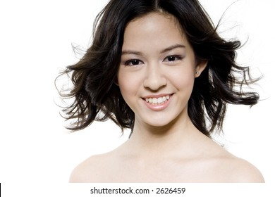 A pretty young woman has her hair blown by a fan on white background