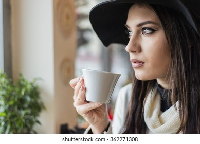 Pretty young woman with hat drinking coffee