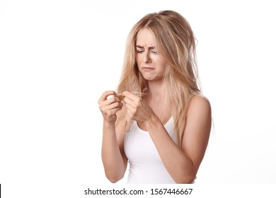 Pretty young woman having a bad hair day standing looking dejectedly at the dry ends of her tousled long blond hair as she holds them up in her hands isolated on white
