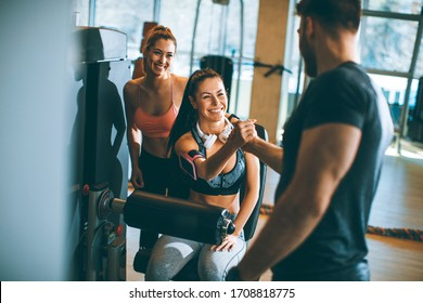 Pretty young woman having exercises on leg extension and leg curl machine in the gym