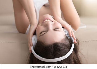 Pretty young woman in headphones lying on sofa listening music or audio book with closed eyes. Joyful beautiful lady enjoying popular songs, relaxing on coach at home. Female music lover portrait