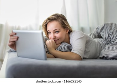 Pretty, young woman in her bed using her tablet computer, staying up to date with news and socail networks she likes(color toned image; shallow DOF)