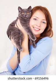 pretty young woman with her cat on the bed at home
