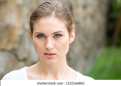 Pretty young woman with her hair tied back off her face outside looking at you