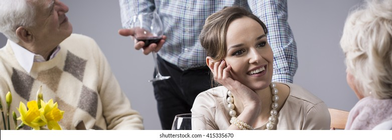 Pretty young woman and her husband on family dinner at parents. Woman talking with mother and man with father-in-law