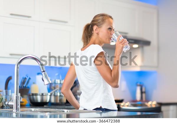Hübsche junge Frau in ihrer modernen, sauberen und hellen Küche, die sich selbst gießt und ein Glas kaltes Leitungswasser trinkt (farbiges Bild); flacher DOF)