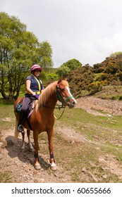 Pretty young woman and her pony enjoying a day out riding in the Shropshire hills, England.