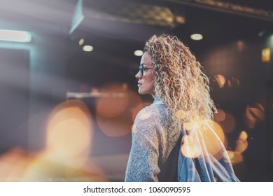 Pretty young woman hipster in stylish clothing wearing eye glasses traveling in the european night city. Bokeh and flares effect on blurred background