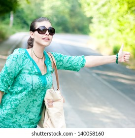 Pretty young woman hitchhiking along a road