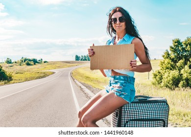 Pretty young woman hitchhiking along a road and waiting on a country road with her suitcase, empty cardboard plate. Beautiful girl in sunglasses hitchhiker. empty Board