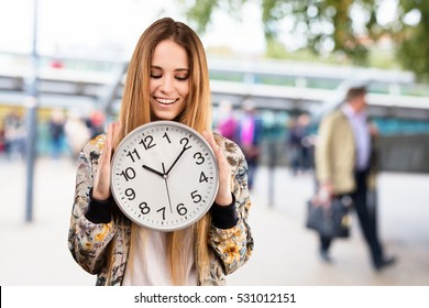 pretty young woman holding a big clock