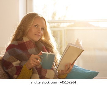 Pretty young woman holding cup of tea and reading book on sofa in front of large window with sun coming through