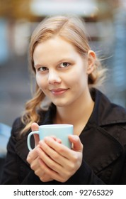 Pretty young woman holding a cup of hot drink outdoors