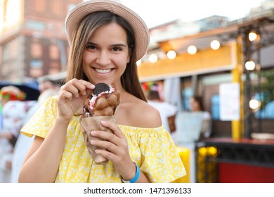 Pretty young woman holding delicious sweet bubble waffle with ice cream outdoors