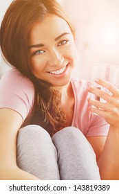 pretty young woman holding glass water smiling