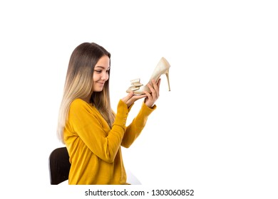 Pretty young woman holding a gorgeous high heel shoe over white background