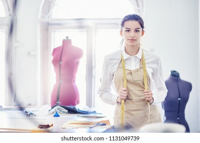 Pretty young woman holding hands on tape measure and looking at camera while standing near table in tailor workshop
