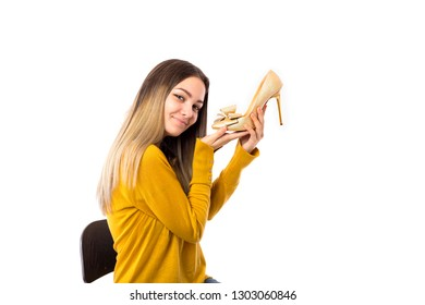 Pretty young woman holding a high heel shoe over white background