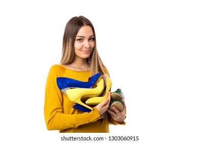 Pretty young woman holding many shoes over white background