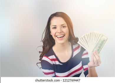 Pretty young woman holding money banknotes on background