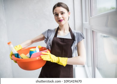 Pretty young woman holding red bucket of cleaning products and smiling to camera, housecleaning concept