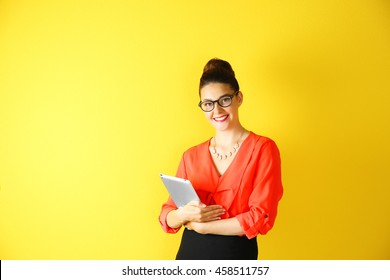Pretty young woman holding tablet on yellow background