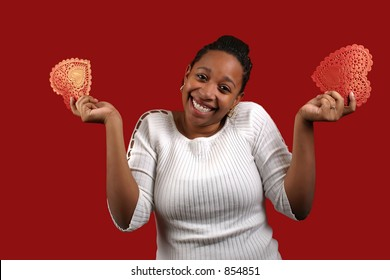 A pretty young woman holding a two paper valentines.