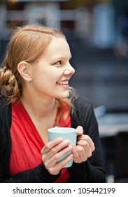 Pretty young woman holds a cup of hot drink in a restaurant outdoors