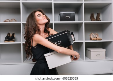 Pretty young woman hugging boxes of shoes around stylish dressing room, wardrobe. She's very happy, pleased, has closed eyes, she bought what she wanted. She wearing black dress, has long curly hair.