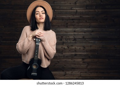 Pretty young woman hugging her guitar, dressed in country style