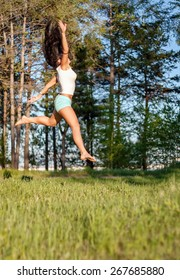 Pretty young woman jumping on green field.