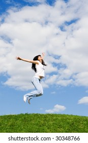 pretty young woman is jumping on green grass