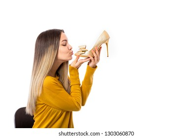 Pretty young woman kissing a high heel shoe over white background.