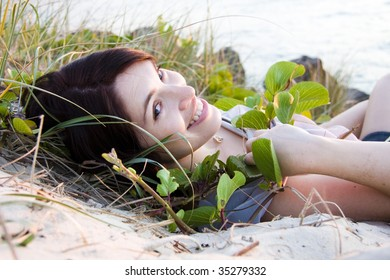 pretty young woman laying on the beach