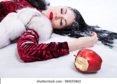 Pretty young woman laying on a snow near the red bitten apple