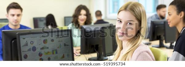 Hübsche junge Frau lernt Computer zu benutzen. Unterricht im College
