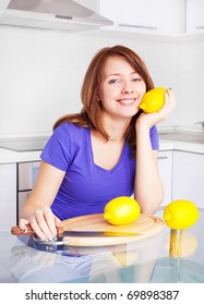 pretty young woman with lemons in the kitchen at home